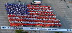 July 4th celebrants in Oviedo, FL show national pride by forming a living flag made up of red, white and blue 100% cotton tee shirts that are 100% Made In America.  (PRNewsFoto/Cotton Incorporated)