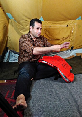 """The 29 year old vet Farooq Saadi from Qamishli in Syria conversing in his tent in the """"Oreokastro"""" refugee camp in Thessaloniki, Greece. On his knee is the life jacket bearing his life story. In October 2016, as part of """"Project Life Jacket"""", the life stories of nine Syrian refugees were illustrated on life jackets used for the crossing to Lesbos.Picture taken on the 7th October 2016 in Thessaloniki. (Project Life Jacket). (PRNewsFoto/Project Life Jacket)"""