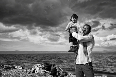 """A father celebrates his family's safe passage to Lesbos after a stormy crossing over the Aegean Sea from Turkey. """"REFUGEE,"""" a groundbreaking exhibit that illuminates the plight of refugees through powerful and evocative photographs will open at the Newseum on Nov. 18. (C)Tom Stoddart"""