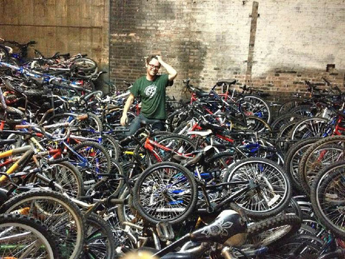 Working Bikes' shop manager, Paul Fitzgerald, wades in a pile of bikes on the Working Bikes shipping dock ...