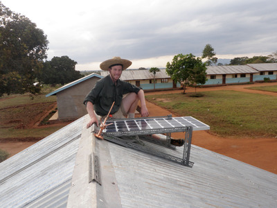 Oregon Tech renewable energy engineering student installs solar panel on Tanzanian village school.