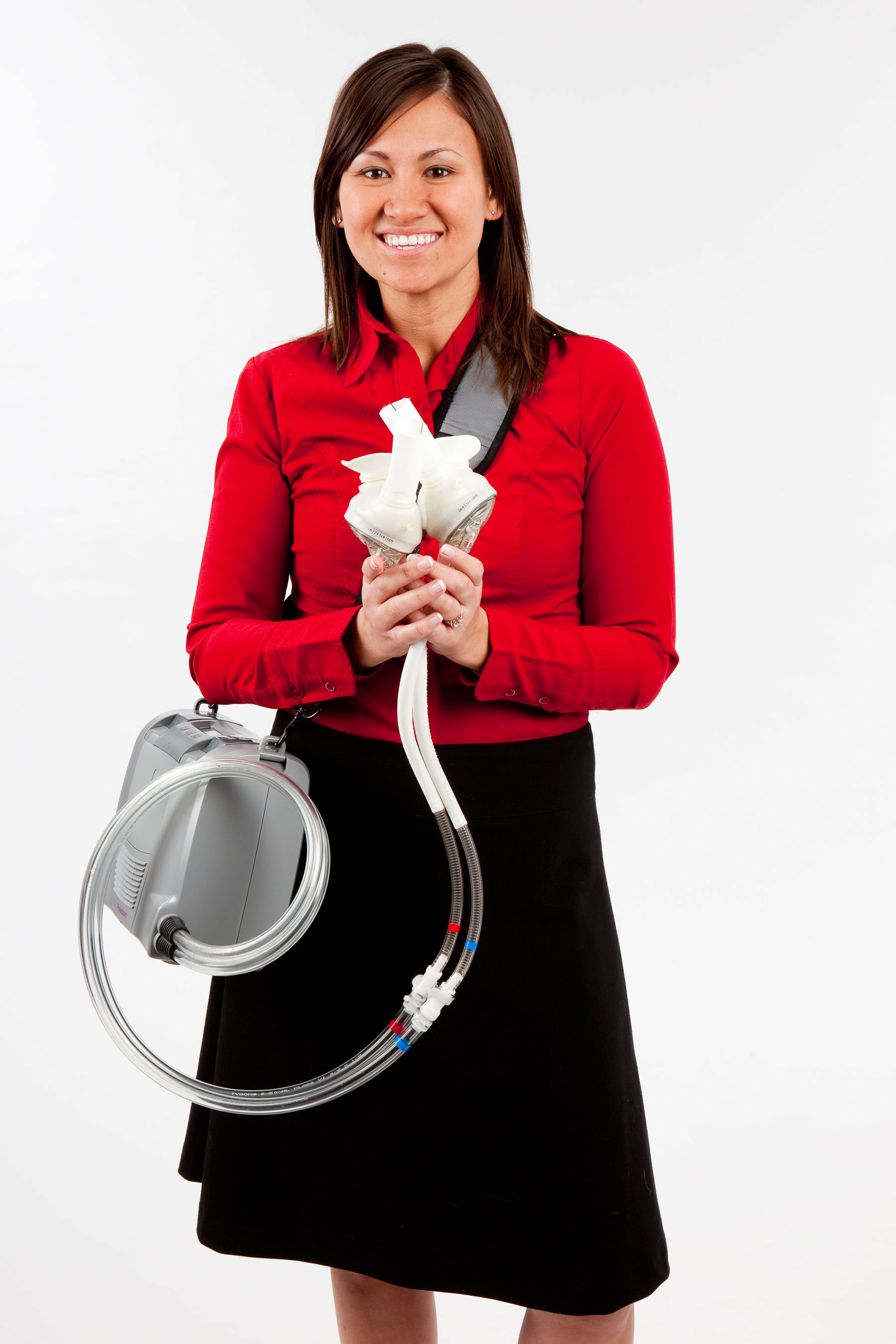Product manager Karen Stamm holds the SynCardia temporary Total Artificial Heart while wearing the Freedom portable driver, the world's first wearable power supply for the Total Artificial Heart.  (PRNewsFoto/SynCardia Systems, Inc.)