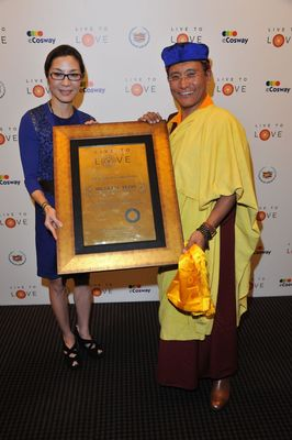 """His Holiness the Gyalwang Drukpa on behalf of the Live to Love Foundation conferring the Global Brand Ambassador status to Michelle Yeoh, internationally acclaimed actress and most recent recipient of France's highest decoration """"the Legion of Honour""""."""