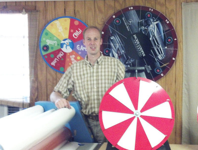 Matt Stahlman pictured with prize wheel.  (PRNewsFoto/Ozark Games LLC)