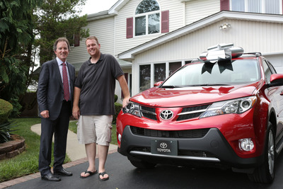 Bill Fay, Toyota Motor Sales, U.S.A., Inc. group vice president and general manager of the Toyota Division, surprises Michael Dee -- Toyota's 50 millionth customer -- with a brand new RAV4 and paid off car loans(PRNewsFoto/Toyota Motor Sales, U.S.A., Inc.)