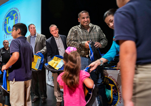 C.R. England COO Brandon Harrison (far left) and President-Mexico Dave Akers (left of center) join other co-sponsors handing out backpacks with school supply vouchers during a giveaway program for children in the United Independent School District in Laredo,TX on Thursday, July 25, 2013, in Laredo, Texas. ((C)2013 Douglas C. Pizac for C.R. England).  (PRNewsFoto/C.R. England, Inc.)