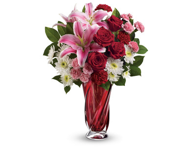 Teleflora's Swirling Beauty Bouquet for Valentine's Day exudes romance with a luxurious mix of luscious red roses and stunning pink lilies perfectly arranged in a swirling, crimson glass vase. (PRNewsFoto/Teleflora)