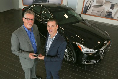 Round Rock Genesis' General Manager, Michael Williams, hands over the keys to the first retail Genesis G90 customer, Russ Johnson (right)