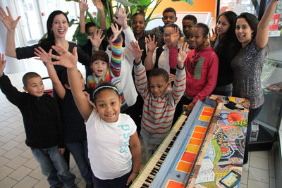 Sing for Hope Co-Founders Camille Zamora and Monica Yunus with kids who benefit from Sing for Hope year-round programming at Betances Community Center. Piano painted by Jillian Logue and photo by Lekha Singh.