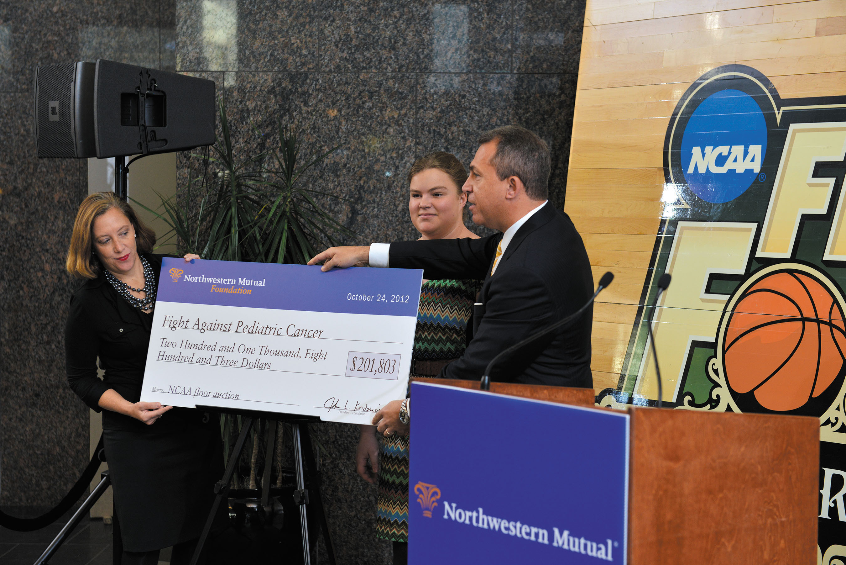 Northwestern Mutual's Dan Rivers unveils the total raised to fight pediatric cancer in Kentucky with Lynnie Myer (left) of Children's Hospital Foundation and cancer survivor Mackenzie Miller.  (PRNewsFoto/Northwestern Mutual)