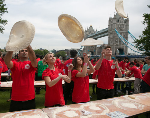 Papa John's employees get stuck in tossing pizza dough as they officially break the GUINNESS WORLD RECORD for the most number of people tossing pizza dough at once. (PRNewsFoto/Papa John's) (PRNewsFoto/Papa John's)