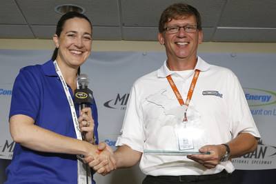 "Consumers Energy Vice President Patti Poppe hands Michigan International Speedway President Roger Curtis the ""On Track to a Greener Michigan"" award to recognize the racetrack's commitment to environmental sustainability."