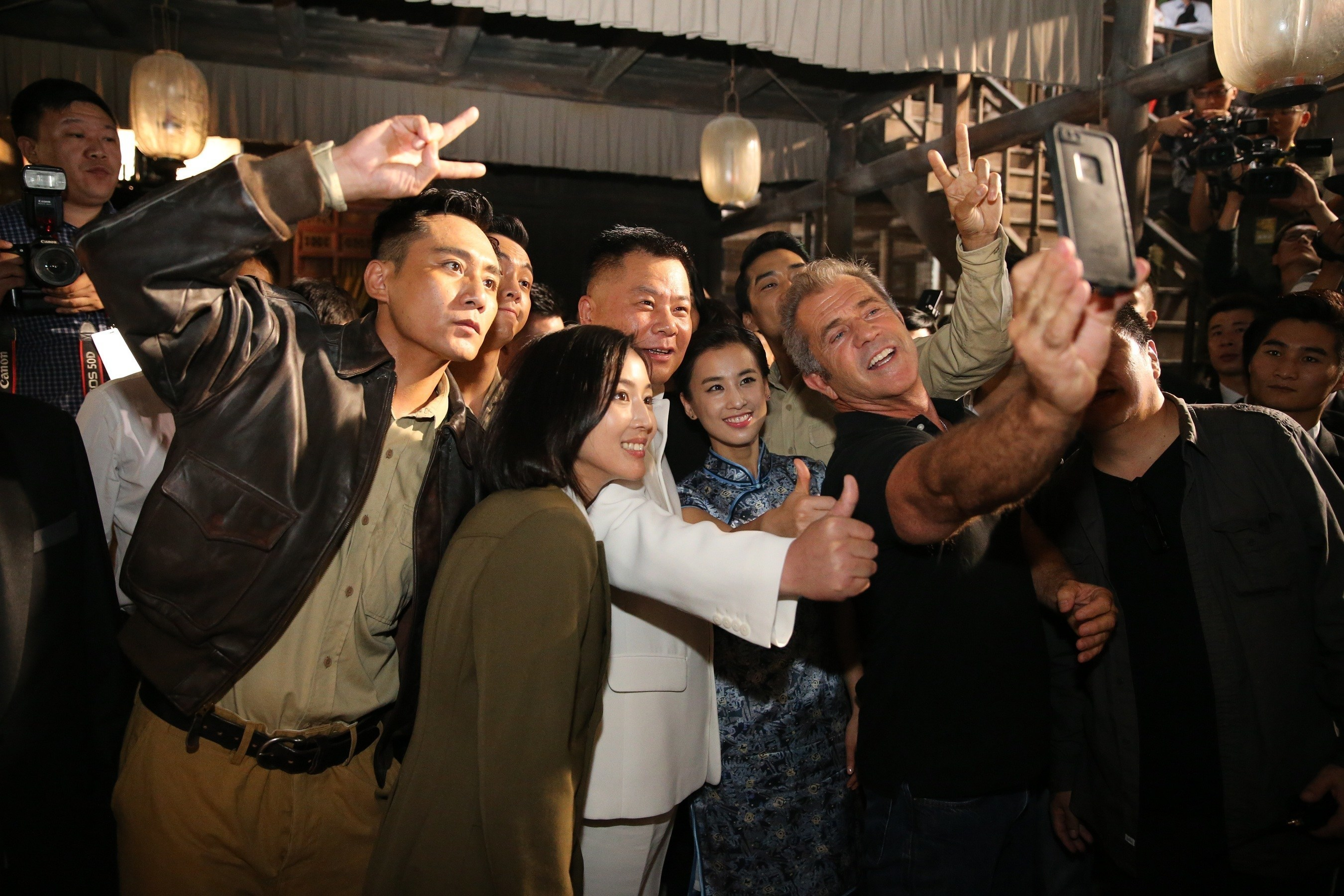 Dr. Shi Jianxiang and Mel Gibson taking a selfie at the conference with Chinese actor Liu Ye and other cast ...