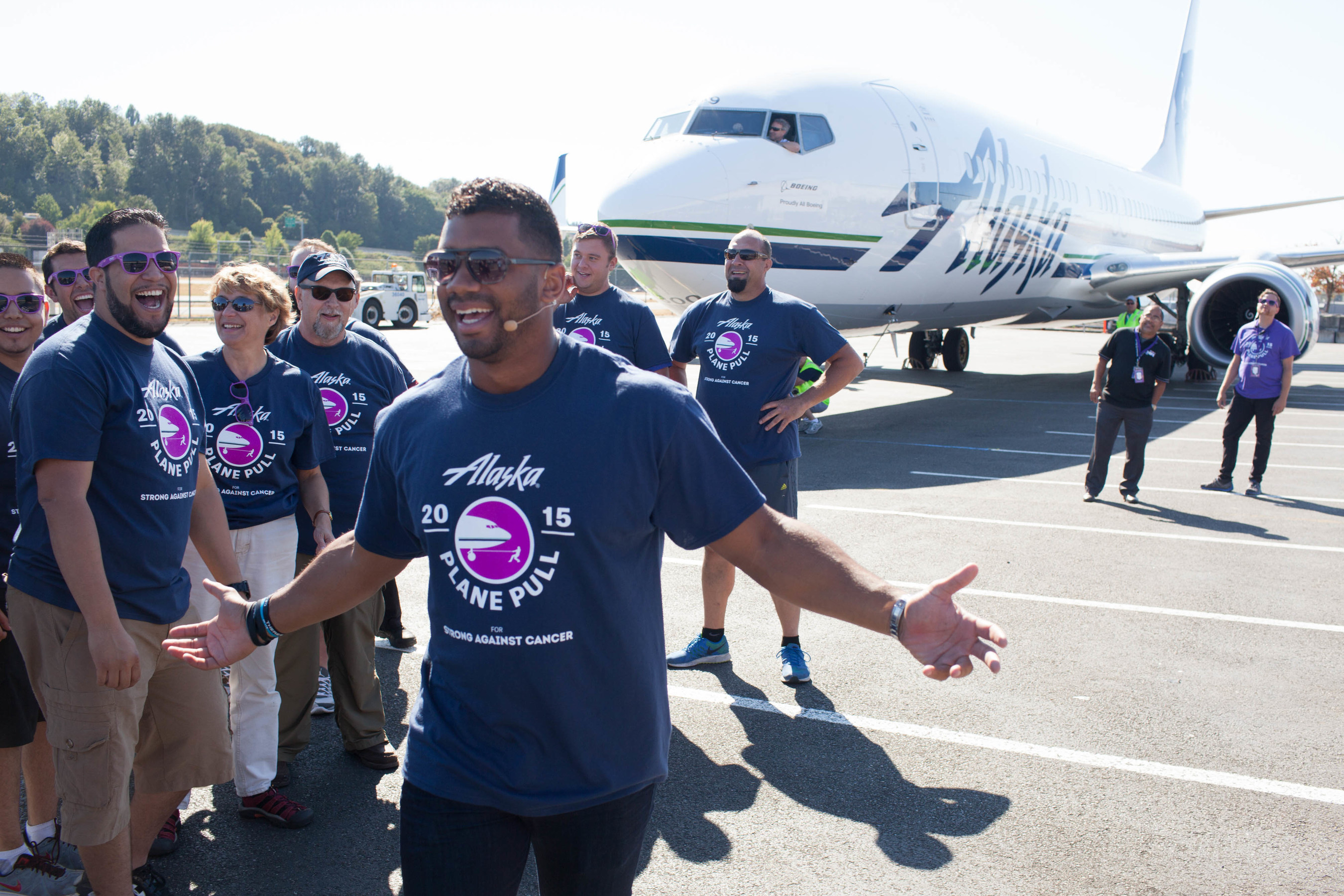Seattle Seahawks Quarterback Russell Wilson pulls a plane during the Alaska Airlines Plane Pull with Joel McHale benefiting Strong Against Cancer at The Museum of Flight in Seattle on Tuesday, July 28, 2015. Team Wilson pulled the 737 in 16.9 seconds, with Team Joel coming in at over a minute.