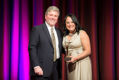 Elaine Bittner, Senior Vice President of Strategic Development, Chesapeake Utilities Corporation (right) receives a Gold Stevie Award for Female Executive of the Year at the 2016 Stevie Awards for Women in Business - presented by Michael Gallagher, President of the Stevie Awards (left).