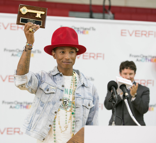 Virginia Beach Mayor Will Sessoms presents Pharrell Williams with a key to the city during a kickoff event at ...