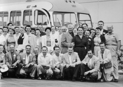 Amway Co-Founders Rich DeVos and Jay Van Andel (bottom row, second and third from the right, respectively) and their group of senior key agents pose with Nutrilite Founder Carl F. Rehnborg and his wife Edith Rehnborg, in front of their tour bus, 1956.