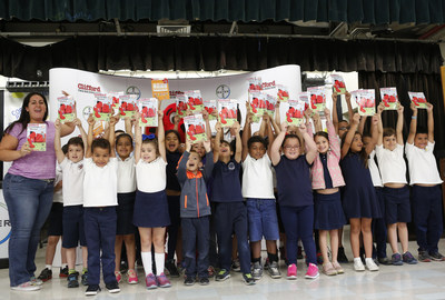 First grade students at Coral Park Elementary School receive their own limited-edition copies of Clifford Goes to the Doctor, by Norman Bridwell and published by Scholastic, on Thursday, May 12, 2016 in Miami, Fla. The story teaches children how to properly care for their pets and includes tips for parents from Bayer Animal Health on pet parasite prevention. Bayer Animal Health will also distribute copies of the book to first grade students throughout the Miami-Dade school district in conjunction with the International Companion Vector-Borne Disease (CVBD) Symposium, held in Miami from May 9-12, 2016. (Brian Blanco/AP Images for Bayer Animal Health)