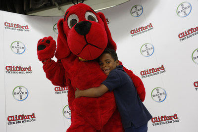 A first grade student at Coral Park Elementary School poses with Clifford the Big Red Dog following a reading of Bayer Animal Health's limited-edition version of Clifford Goes to the Doctor, by Norman Bridwell and published by Scholastic, on Thursday, May 12, 2016 in Miami, Fla. The story teaches children how to properly care for their pets and includes tips for parents on pet parasite prevention, and its release corresponds with Bayer Animal Health's International Companion Vector-Borne Disease (CVBD) Symposium, held in Miami from May 9-12, 2016. (Brian Blanco/AP Images for Bayer Animal Health)