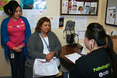 Diana Jimenez receives her Pap test and mammogram results during the See, Test & Treat(R) on Oct. 9-11 at NorthPoint Health & Wellness Clinic, Minneapolis, Minn.  As Dia Xiong, RN, explains the results, NorthPoint employee, Imelda Trevino assists by providing translation services.  The program, funded by a grant from the College of American Pathologists (CAP) Foundation, brings free, same-day cervical and breast cancer testing, diagnosis, and follow-up care to medically underserved women. This patient-centered approach helps ensure that underserved women gain the early detection advantage and life-saving services that pathologists provide.  (PRNewsFoto/College of American Pathologists)