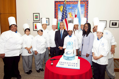 Student chefs from the Washburne Culinary Institute of City Colleges of Chicago, along with City Colleges Chancellor Cheryl Hyman (grey suit) and Washburne's Provost William Reynolds (left of Mayor Emanuel) present Chicago Mayor Rahm Emanuel with a cake celebrating the City Colleges of Chicago centennial.