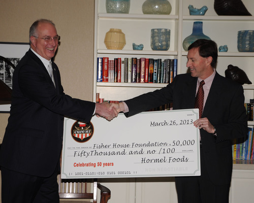 Jeffrey M. Ettinger, president and chief executive officer of Hormel Foods (right) and David Coker, Fisher House Foundation president (left) present $50,000 and food for Easter meals to Fisher Houses across the country, on behalf of Cure 81(R) ham brand.  (PRNewsFoto/Hormel Foods)