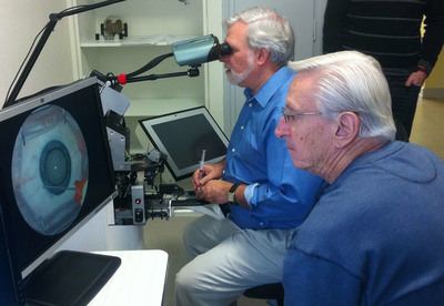 HelpMeSee simulator development team, Dr. M. Glenn Strauss, Chief Medical Officer, and Dennis Gulasy, Director of Engineering and Simulation Systems evaluate the Prototype (proof of concept) of HelpMeSee MSICS Eye Surgery Simulator by Moog (Photo courtesy of HelpMeSee).  (PRNewsFoto/HelpMeSee)
