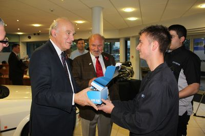 Secretary of State, Vince Cable - who visited Cosworth today to show his support for the company's plans to create a new factory - is presented with an engraved Formula One piston by Cosworth apprentices, Charlie Bailey and Toby Hibble. From L - R: The RT Hon Dr. Vince Cable MP, Kevin Kalkoven (chairman, Cosworth), Charlie Bailey (apprentice, Cosworth), Toby Hibble (apprentice, Cosworth) (PRNewsFoto/Cosworth Group)