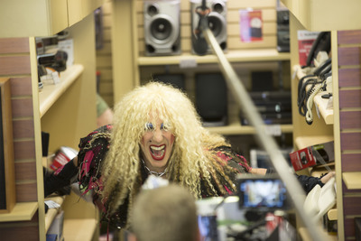 Twisted Sister front man Dee Snider uses a trademark move in this behind-the-scenes shot from RadioShack's Super Bowl ad. Snider helps tear apart an outdated store to usher in a new look and new positioning for the brand.  (PRNewsFoto/RadioShack Corporation)