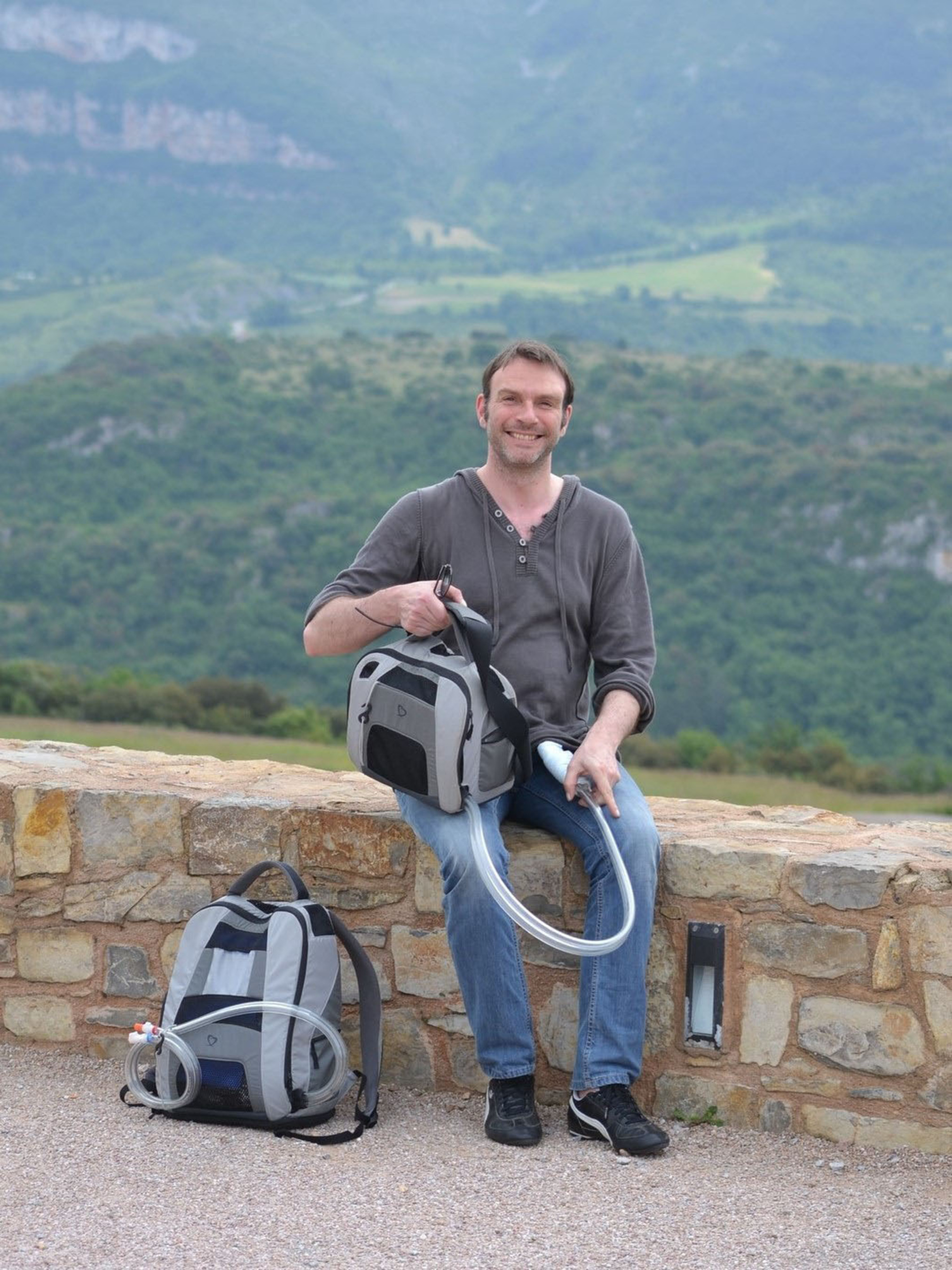 On Aug. 5, 2013, Frederic Thiollet surpassed two years of support with the SynCardia Total Artificial Heart. In the Shoulder Bag he's holding is the Freedom(R) portable driver, which powers his Total Artificial Heart. The Backpack on the ground contains his back-up Freedom driver and extra batteries.  (PRNewsFoto/SynCardia Systems, Inc.)