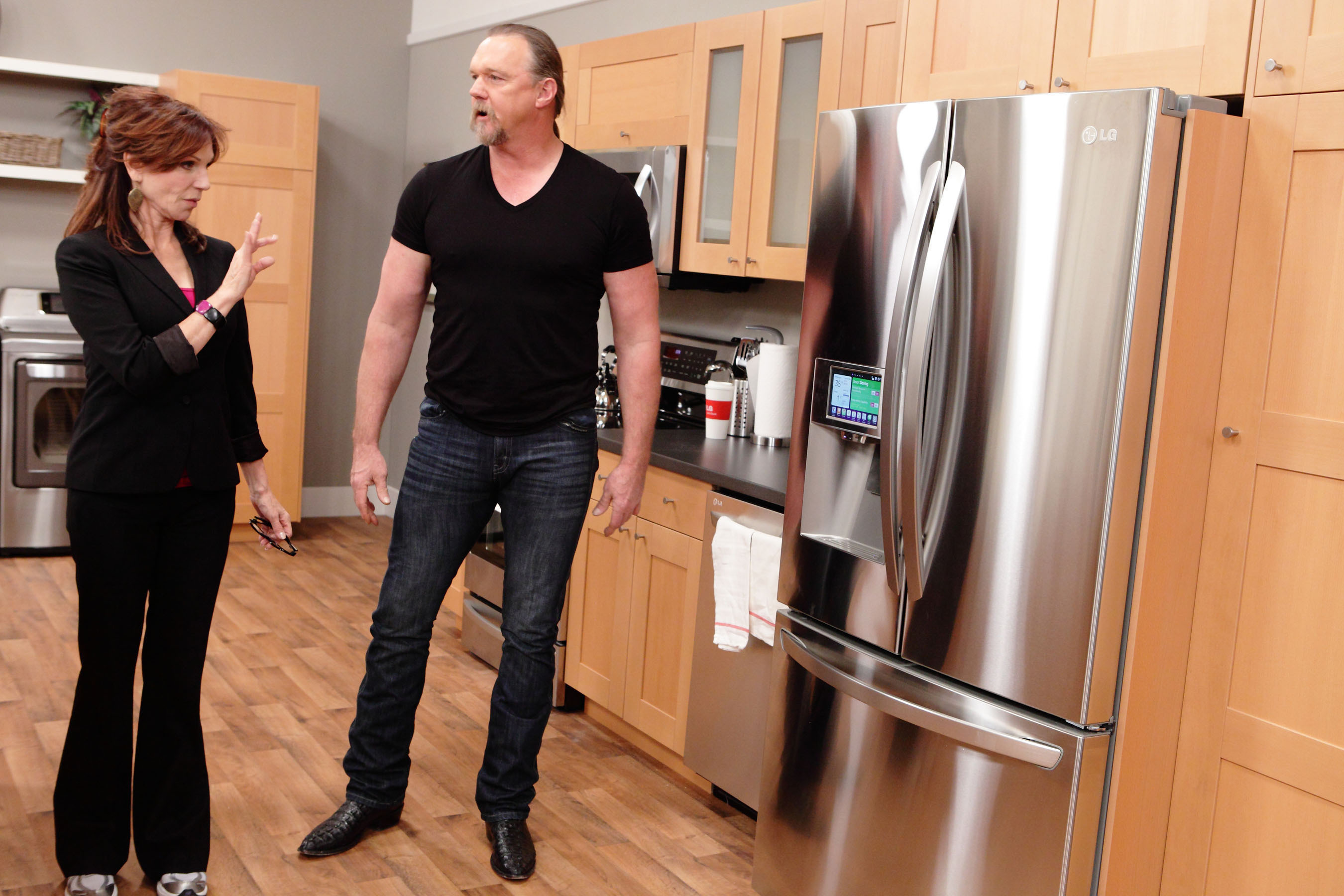 Marilu Henner and Trace Adkins brainstorm how to incorporate LG's Smart Refrigerator into Team Power's marketing presentation airing during the LG episode on NBC this Sunday, April 28, at 9 p.m. ET/8 p.m. CT.  (PRNewsFoto/LG Electronics USA, Inc.)