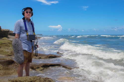 Veteran radio journalist Alex Chadwick, host of public radio's BURN: An Energy Journal, stands at water's edge with recording gear on Blowing Rocks Beach, north of Fort Lauderdale, Florida.  Chadwick hosts the upcoming one-hour BURN special, ...