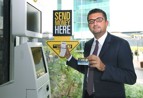 Jean Claude Farah, President, Middle East, Africa, Asia Pacific, Eastern Europe & CIS, Western Union having just completed a transaction using the automated self-service money transfer kiosk located in Dubai Internet City (PRNewsFoto/Western Union)