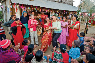 A solo traveler with Overseas Adventure Travel (OAT) shares a dance in Birethanti, Nepal.  Today, 44 per cent of OAT travelers book solo, despite marital status, up from 35% in 2013.  Eight in 10 solo travelers are women.