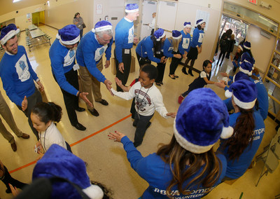 Students at Houston ISD's Crespo Elementary give high-fives to BBVA Compass volunteers ahead of the kickoff event for the bank's Project Blue Elf initiative. The initiative will promote financial literacy and deliver toys to 5,000 children at schools in 27 markets across the bank's footprint, including 430 kindergarten, first- and second-grade students at Crespo.