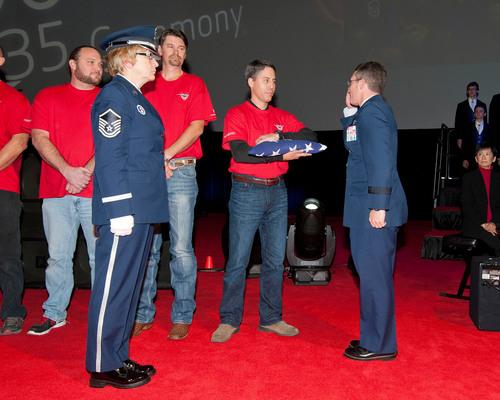 Brig. Gen. Michael Rothstein accepts commemorative U.S. flag from Chris Felton, a Lockheed Martin F-35 ...