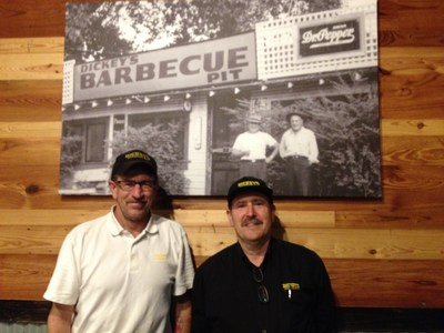 Local owner, John Sanchez and his general manager stand in front of a photo of the original Dickey's Barbecue location in Dallas, Texas. (PRNewsFoto/Dickey's Barbecue)