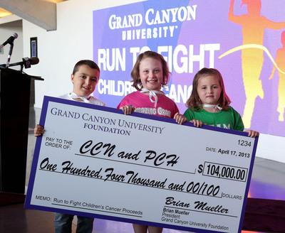 Cancer-fighting Superheroes Cooper Gokee, Grace Kostyk and Olivia Baumgardner present $104,000 to Phoenix Children's Hospital, Children's Cancer Network on behalf of Grand Canyon University.  (PRNewsFoto/Grand Canyon University)