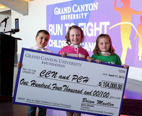 Cancer-fighting Superheroes Cooper Gokee, Grace Kostyk and Olivia Baumgardner present $104,000 to Phoenix Children's Hospital, Children's Cancer Network on behalf of Grand Canyon University.  (PRNewsFoto/Grand Canyon University)