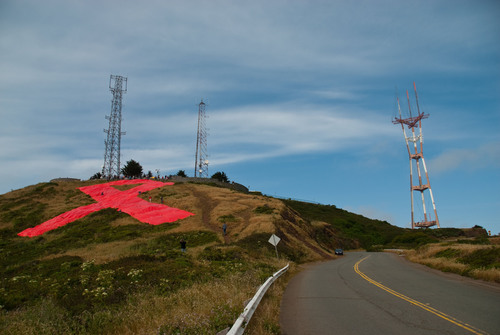 Volunteers put the finishing touches on the first-ever giant red ribbon on San Francisco's Twin Peaks to ...