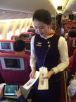 Hainan Airlines flight attendants distributing Change for Good donation bags to passengers