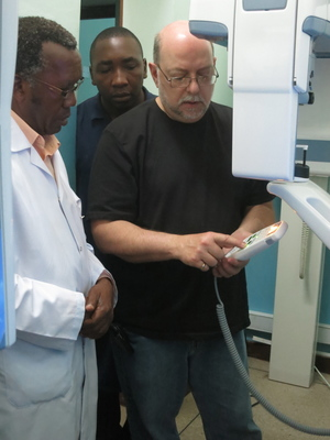 (Pictured L to R) Dr. Elison Simon, Dean of MUHAS School of Dentistry, and Haruna Matwili, an equipment repair technician at Muhimbili University, look on as Jules Paoletti, Henry Schein Eastern US Special Markets Manager, demonstrates how to use a digital panoramic X-ray machine.  (PRNewsFoto/MCW)
