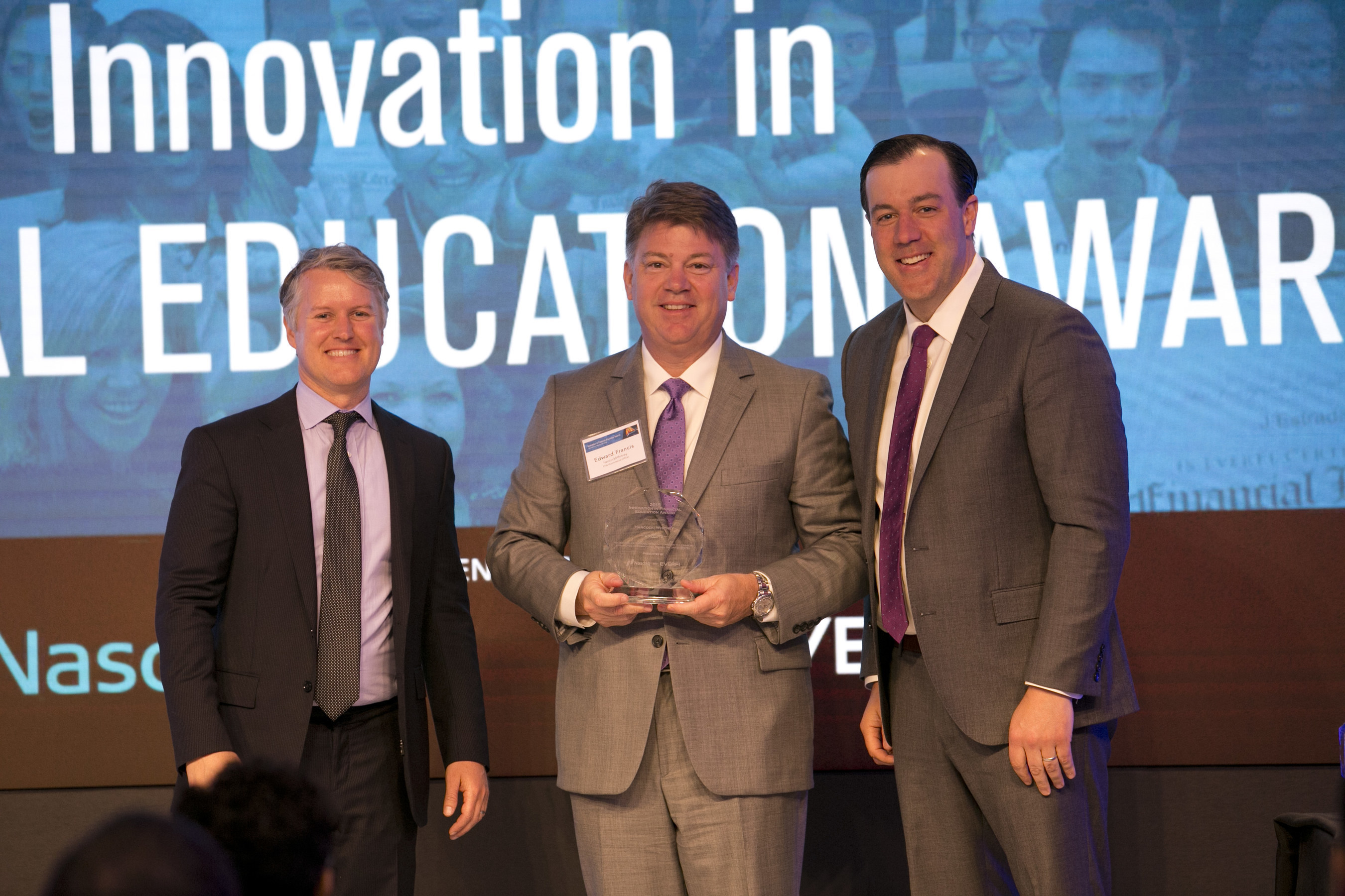 Hancock Holding Company Chief Banking Officer Edward G. Francis (center) accepts the Innovation in Financial Education Award from EverFi, Inc., co-founders CEO Tom Davidson (left) and Chief Strategy Officer Jon Chapman at Nasdaq's Marketsite headquarters in New York City.