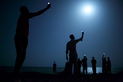 """African migrants crowd the moonlit Djibouti shore trying to capture cell phone signals from neighboring Somalia to contact relatives abroad. """"Signal"""" won first place in the Feature category in Pictures of the Year International, one of the oldest and most prestigious photojournalism contests in the world. Credit: John Stanmeyer, Freelance (PRNewsFoto/Newseum )"""