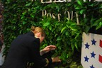 Lieutenant Colonel Paula Smith, USA places a plant in the Code of Support Foundation's Living Wall to honor one of the fallen female service members who lost their lives in the wars in Iraq and Afghanistan. The Living Wall of Honor exhibit will remain on display at the Women's Memorial through October. (PRNewsFoto/Code of Support Foundation)