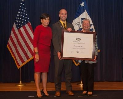 "Secretary Pritzker presenting Masterclock with Presidential ""E"" Award"