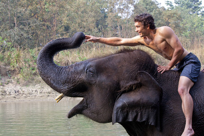Biggest & Baddest star Niall McCann at the river with his domestic elephant in Nepal.  A supreme athlete and biologist, Niall is James Bond/Tarzan and Indiana Jones rolled into one.  He will ride this elephant into the jungle to discover huge rare prehistoric-looking Asian elephants...one of these monsters chases him up a tree.   Later, Niall will come face to face with charging Bengal tigers, whose numbers are now hugely depleted due to poaching for body parts.  Watch the six-part series produced by Wild Planet Productions on Velocity Channel starting January 5th, 2013.  (PRNewsFoto/WILD PLANET PRODUCTIONS)