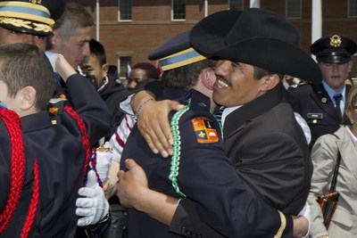 """Leo Alvarado, Spanish teacher and soccer coach at St. John's Military School in Salina, Kansas, hugs a graduate and former student at Commencement. Teachers and staff at St. John's place a strong emphasis on building relationships with cadets and their families. St. John's was recently recognized for placing a strong emphasis on engaging families in their child's education and social development as well as the school's commitment to ensuring each cadet is supported by at least one adult advocate. Many former students stay in touch with their teachers and """"St. John's Moms"""" long after graduation."""