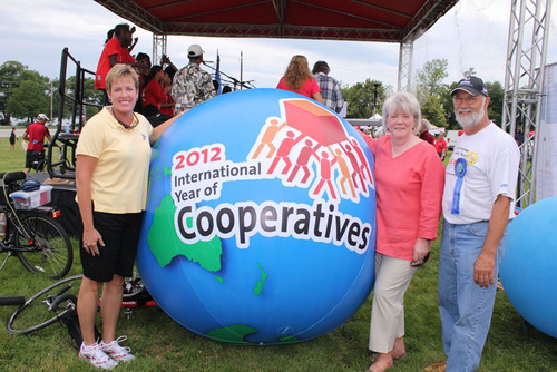 Ann Lewis (left) Rappahannock Electric Cooperative Director of Communications and Public Relations with Liz Bailey (center) Interim President and CEO of the National Cooperative Business Association; and Walter Fletcher (right), Board Treasurer, Cabot Creamery Cooperative, next to a 2012 International Year of Cooperatives Globe during festivities at the Celebrate Portland event honoring the IYC on July 7 in Portland, Maine.   (PRNewsFoto/Cabot Creamery Cooperative)