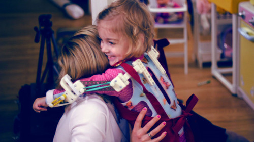 "The design of Emma's ""magic arms"" exoskeleton, which lets her play and hug like other kids, has ..."